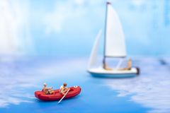Miniature people, Rowing boat in the ocean. Image use for sports concept.  Stock Photos