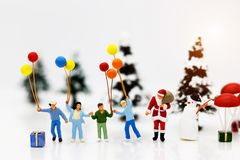 Miniature people: Santa Claus and childrens holding balloon with Christmas Tree. stock image
