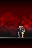 Miniature people -  a senior  couple in love. Miniature people -  a senior couple in love take a selfie in a red blur background Stock Image