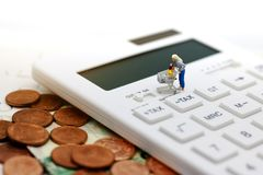 Miniature people with shopping cart on calculator and coins. royalty free stock image