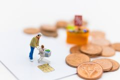 Miniature people with shopping cart using as background business concept. Miniature people with shopping cart by credit card using as background business concept Royalty Free Stock Photo