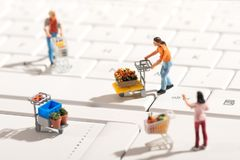 Miniature people shopping for items with carts Royalty Free Stock Photography