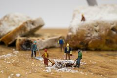 Miniature people shoveling snow from board. Concept Miniature people shoveling snow from board Stock Photo