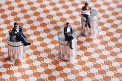 Miniature people sitting. Miniature people in action in various situations Stock Photo