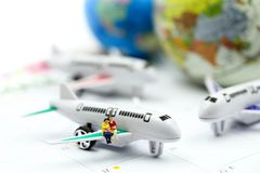 Miniature people : sitting with airplane,for travel around the world concept.  stock image