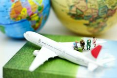 Miniature people : sitting on airplane wing for travel around th royalty free stock photos