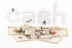 Miniature people sitting on cash wooden letters and coins stock photography