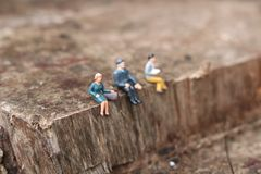 Miniature people sitting down on ledge. royalty free stock photography
