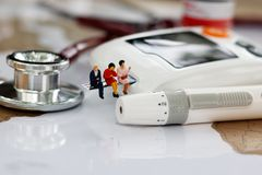 Miniature people sitting on glucose meter of diabetes and stethoscope on world map. Healthcare, stock photography
