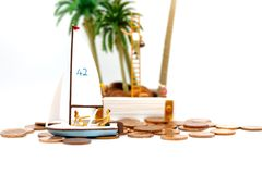 Miniature people sitting on a sailboat that grooves on coins mon stock photo