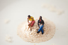 Miniature people sitting on a stack of sand Royalty Free Stock Image