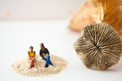 Miniature people sitting on a stack of sand Royalty Free Stock Photos