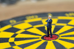 Miniature people small brave confident figure  businessman stand. Ing at the center of dartboard as business goal achievement concept Royalty Free Stock Photography