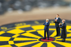 Miniature people small figure businessman standing at the center Royalty Free Stock Photos
