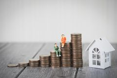 Miniature people small figure sit on coin money stack step up growing growth with model white house, Property investmen royalty free stock image