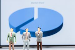 Miniature people : small figures businessmen stand with graph ma stock photo