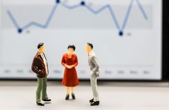 Miniature people : small figures businessmen stand with graph on stock photos