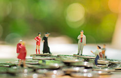 Miniature people: small figures businessmen stand on top of coins. Business Growth concept.  Royalty Free Stock Images
