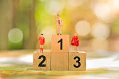 Miniature people: Small worker figures with wooden podium standing. Business team competition concept Royalty Free Stock Image