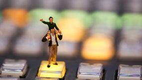 Miniature people : Son riding on father`s shoulders on switcher. Control of Television Broadcast,color buttons Stock Photo