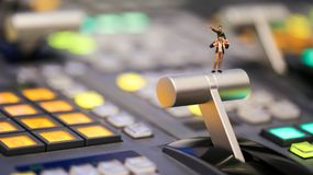 Miniature people : Son riding on father`s shoulders on switcher. Control of Television Broadcast,color buttons royalty free stock image
