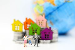 Miniature people: standing on coins stack with house, money savi stock photo