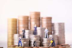 Miniature people standing on a pile of coins. Inequality and social class. royalty free stock image