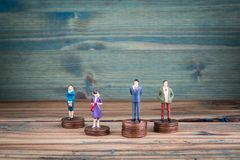 Miniature people standing on piles of coins stock image