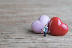 Miniature people sweet couple with red and pink heart shapes on. Wooden table using as Valentines or wedding card and background with copy space Stock Photography