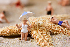 Miniature people in swimsuit on the beach royalty free stock image
