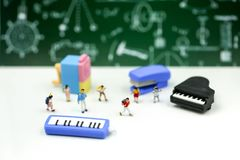 Miniature people : Teacher and students , children with School s. Upplies and piano , Back to school concept stock photography