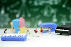 Miniature people : Teacher and students , children with School s. Upplies and piano , Back to school concept stock photos