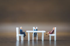 Miniature people team sitting down on the chair Royalty Free Stock Image