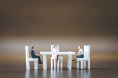 Miniature people team sitting down on the chair Stock Image