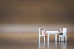Miniature people team sitting down on the chair Stock Photo
