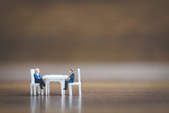 Miniature people team sitting down on the chair Stock Photography
