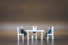 Miniature people team sitting down on the chair Stock Images