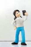 Miniature people, a teenage girl makes a selfie. Stock Photo