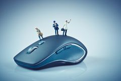 Miniature people on top of computer mouse. Business concept Stock Image