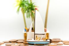 Miniature people: Tourists cruise on coins. Image use for promote tourism, travel concept Stock Image