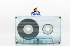 Miniature people: Tourists cycling  on Compact Cassette. Image use for music of travel, business concept Royalty Free Stock Photo