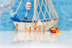 Miniature people: Tourists swimming with boat. Concept of travel Stock Photography