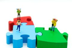 Miniature people: Tourists walk on colorful jigsaw. Image use for travel business concept Stock Photos
