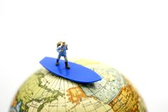 Miniature people : traveler on surfboard with world map, backpac. K and travel concept Royalty Free Stock Photography