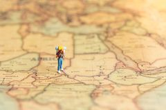 Miniature people : traveler walking on the map. Used to travel to destinations on travel business background concept.  Stock Photos