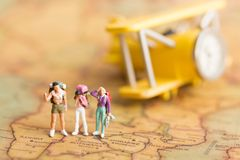 Miniature people: travelers with backpack standing on world map travel by plane Used as a travel business concept.  Royalty Free Stock Image