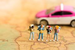 Miniature people: travelers with backpack standing on world map travel by taxi. Used as a travel business concept.  Stock Photos