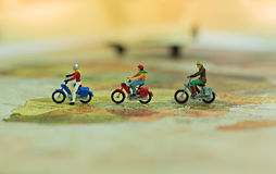 Miniature people, travelers with bicycle on world map, cyling to destination. Miniature people, travelers with bicycle on world map, cyling to destination Royalty Free Stock Photography