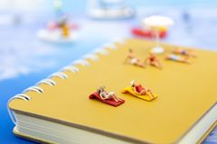 Miniature people: Travelers lie sunbathe on the book brown and blue ocean. Image use for vacation, summer, relax time concept.  stock photo