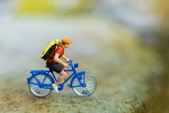 Miniature people : Travelers riding bicycle on the rugged road using as background traveling  business concepts.  Royalty Free Stock Photography
